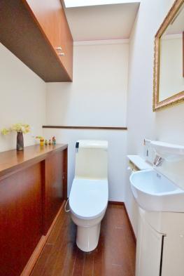 大容量の収納棚を備えた、天窓付き2階のトイレスペース。明るくすっきりと清潔感溢れた空間です。ウォシュレット、手洗いカウンター付きです。